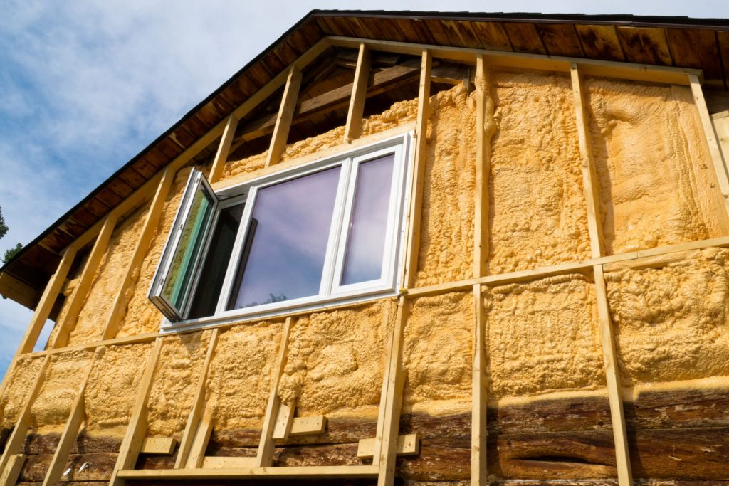 Fiberglass insulation applied on the middle wooden framing of a house