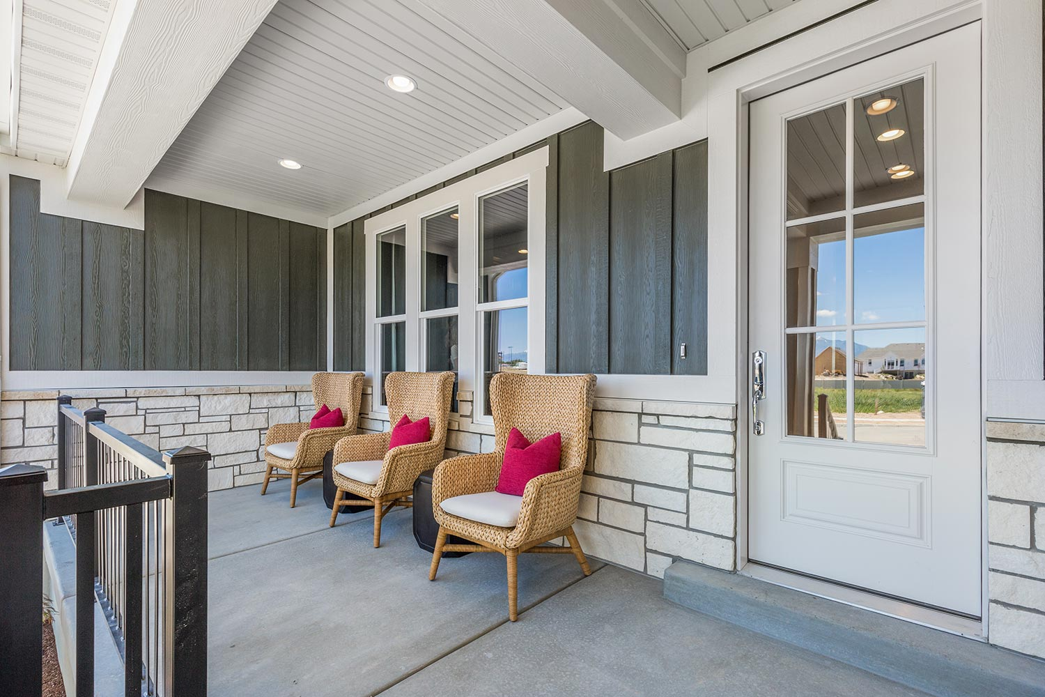 Front porch of a house with rattan chairs and concrete floor