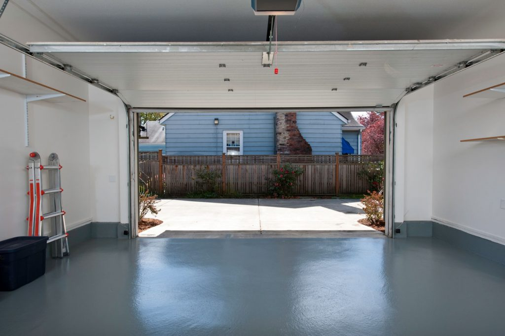 Interior of an empty garage with epoxy flooring and white painted walls