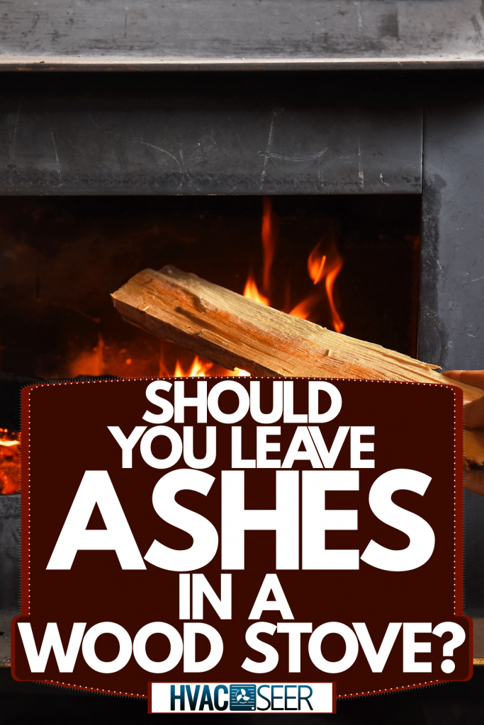 A man putting a small block of fire wood to the wood stove, Should You Leave Ashes In A Wood Stove?