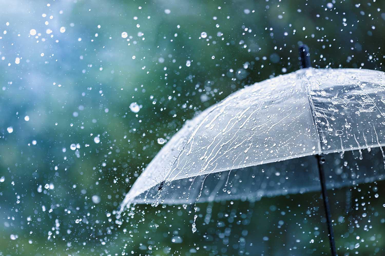 Transparent umbrella under rain against water drops splash background