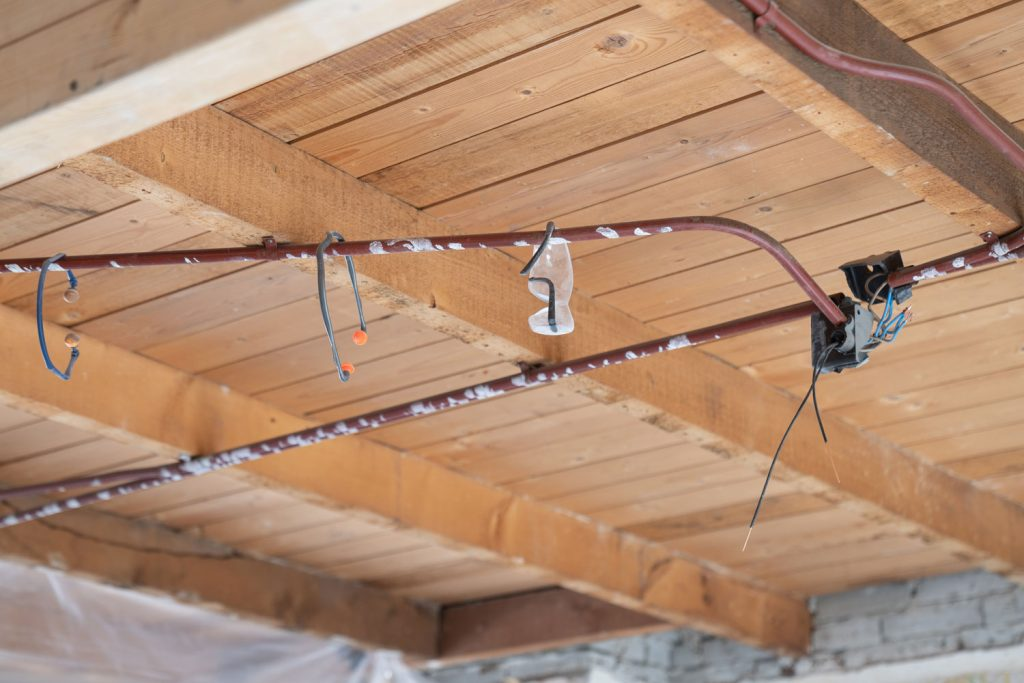 Uninsulated ceiling of a house with visible copper tubings for electricity
