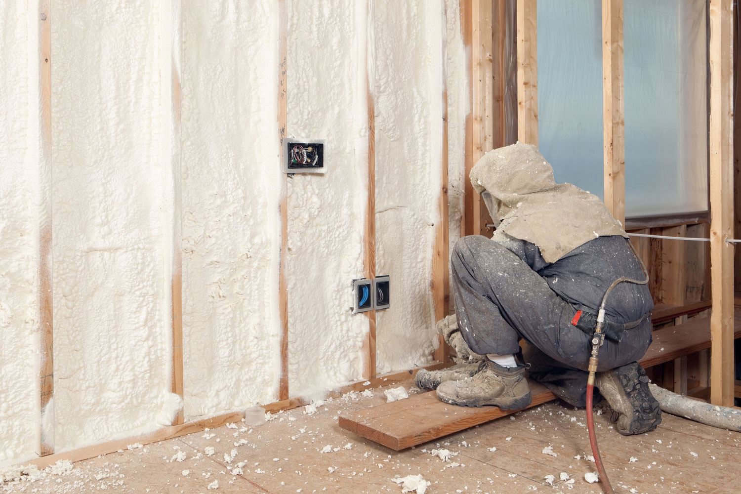 Worker Spraying Expandable Foam Insulation between Wall Studs, Spray Foam Temperature Settings [Cold And Hot Climate Issues]