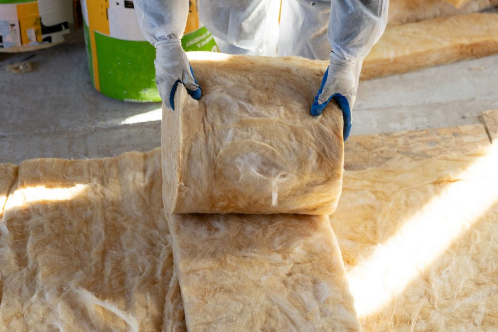 A worker unrolling rockwool insulation for the atticA
