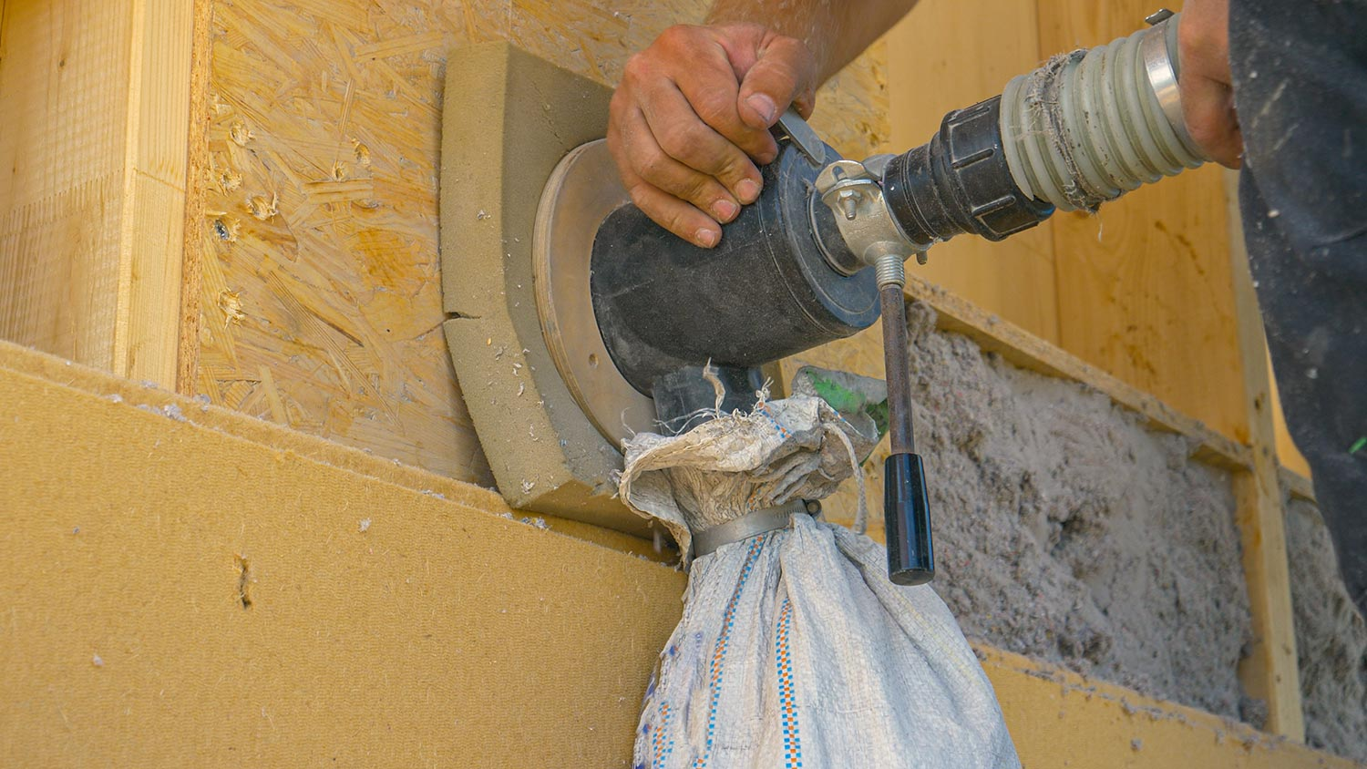 Builder uses a blower to insulate the wood wall with recycled paper