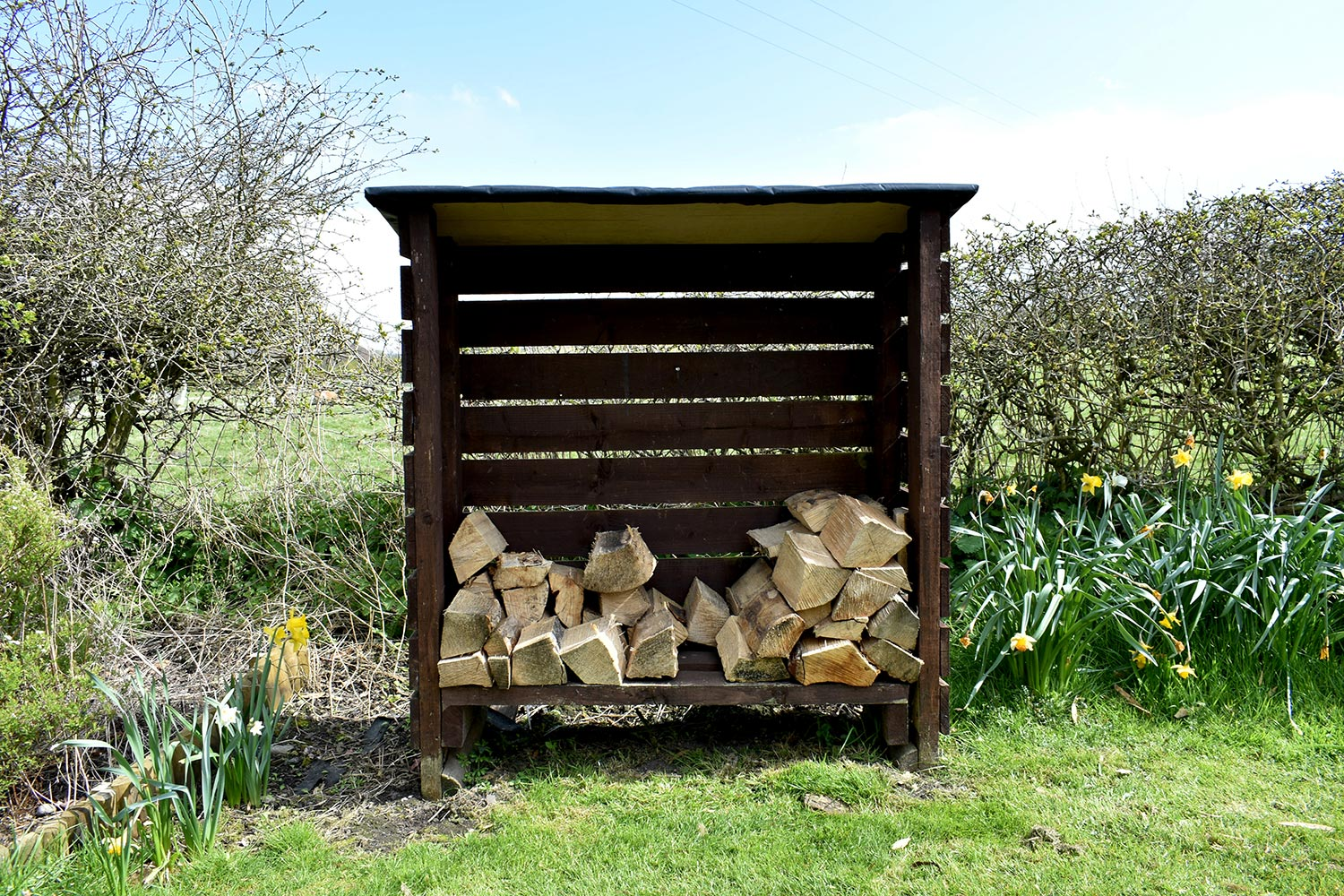Close up of wooden slated storage box containing cut logs