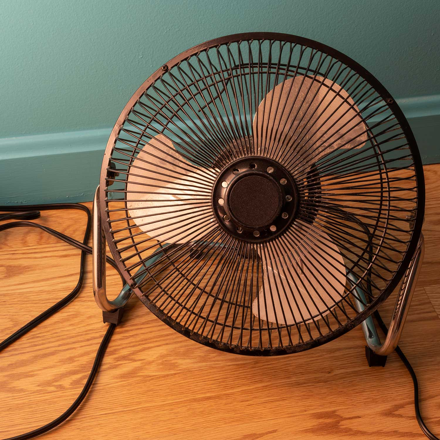 Small round black electric fan on wood floor