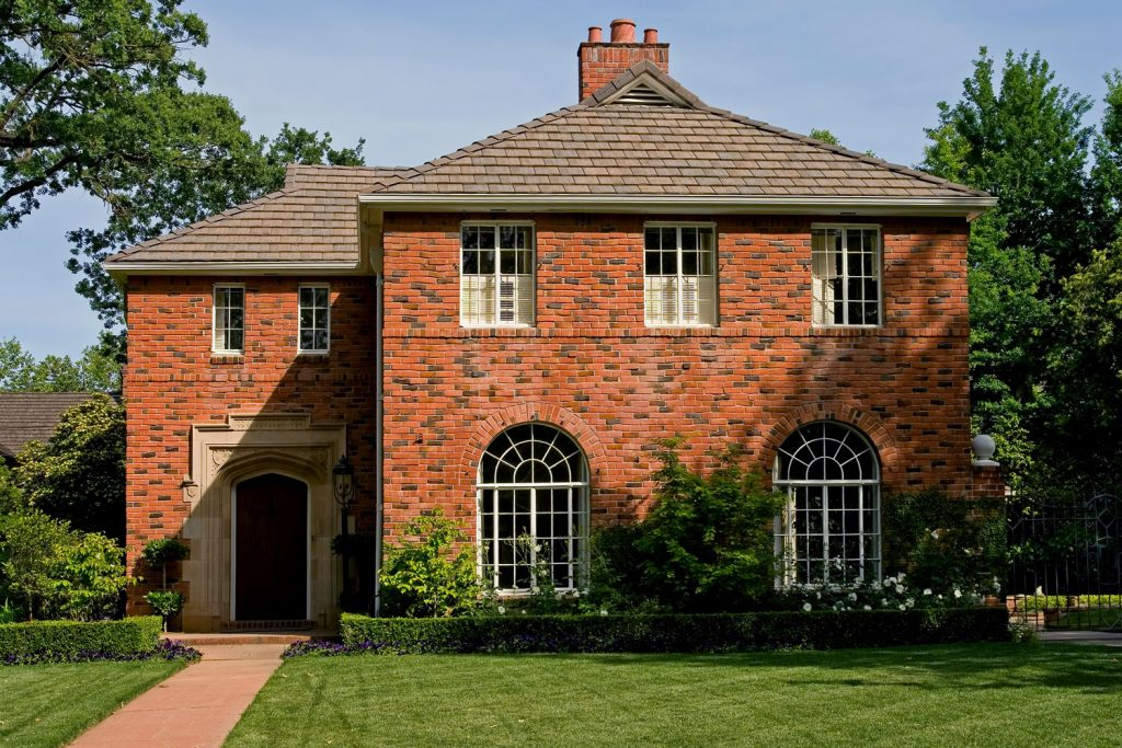 Two storey luxurious red brick house with a well maintained landscaping