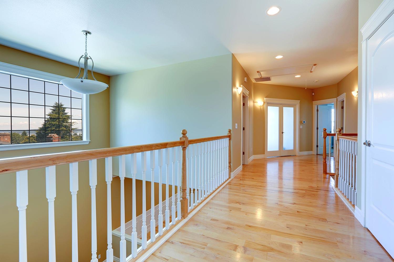 Upstairs hallway with shiny hardwood floor and white railings