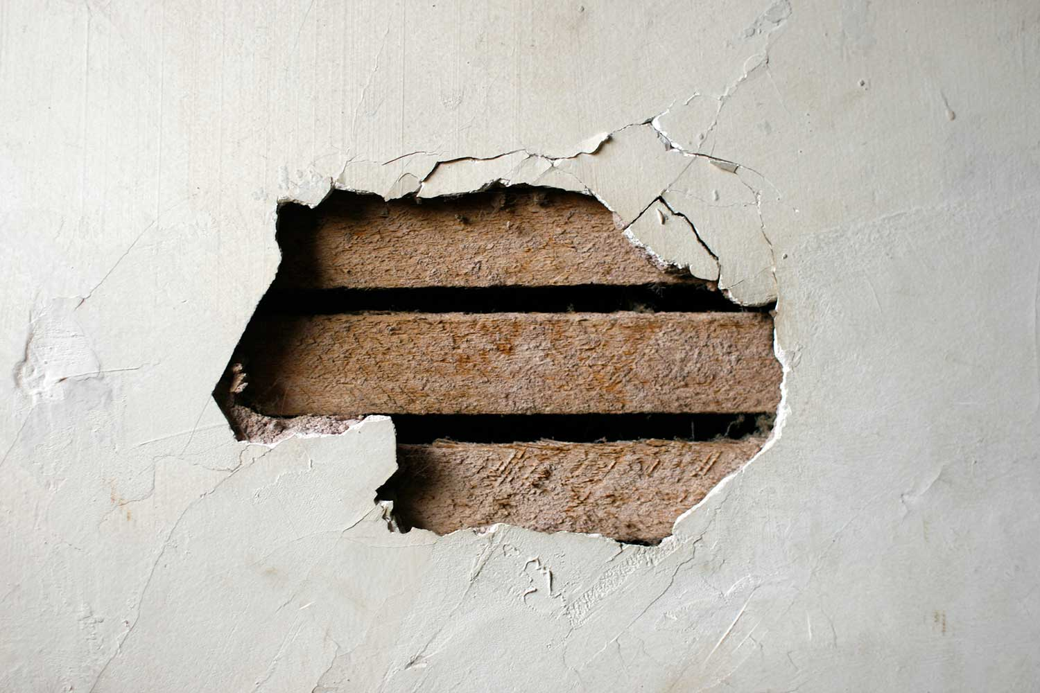 Close up of a hole in a plaster wall