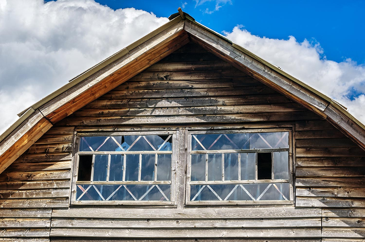 Gable end of an aged cottage with horizontal wooden siding and windows