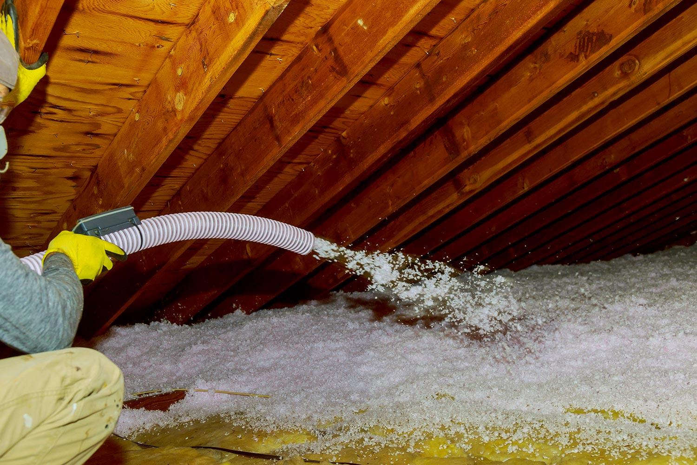 Technician spraying blown fiberglass insulation between attic trusses