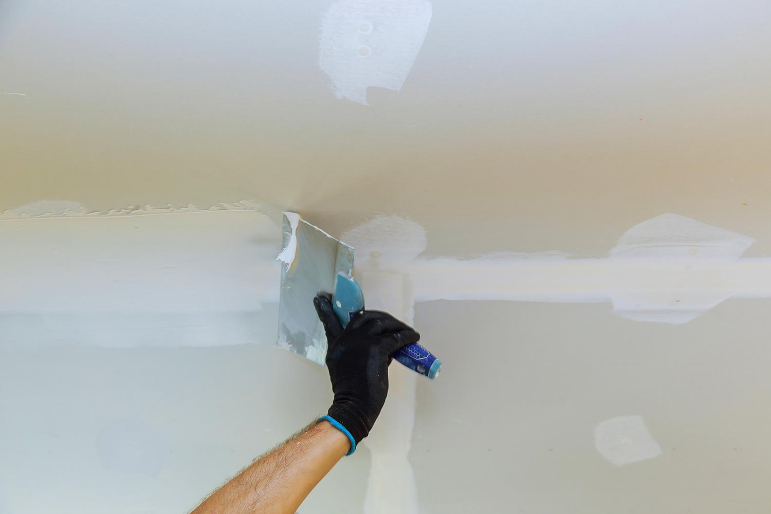 Worker puttied wall using a paint spatula